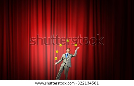Young businessman in cap on stage juggling with balls #322134581