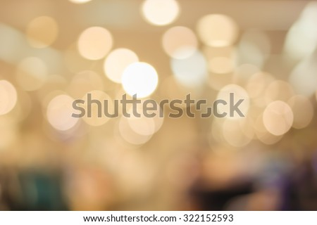 abstract blurred bokeh light in department store with warm tone color background concept.