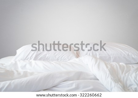 Close up white bedding sheets and pillow on natural stone wall room background, Messy bed concept #322260662