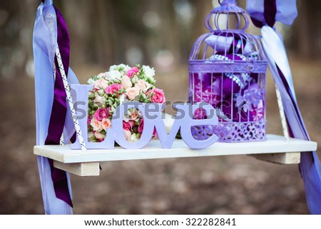 Wedding decoration of a beautiful delicate bouquet lying down on a swing #322282841
