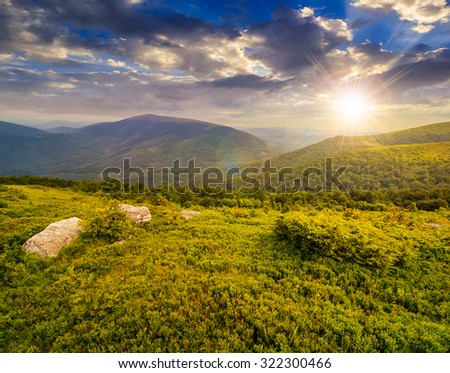 meadow  with white boulders on the hill of mountain range in evening light #322300466
