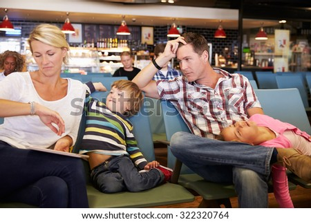 Family In Airport Departure Lounge Wait For Delayed Flight Royalty-Free Stock Photo #322320764