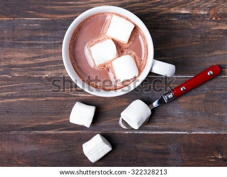 Cup of hot cocoa with marshmallows on the wooden table, top view