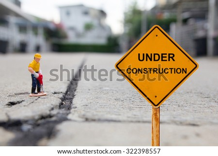 small figure of a man digging concrete street with Under Construction message.