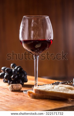 Pouring red wine glass against wooden background #322571732
