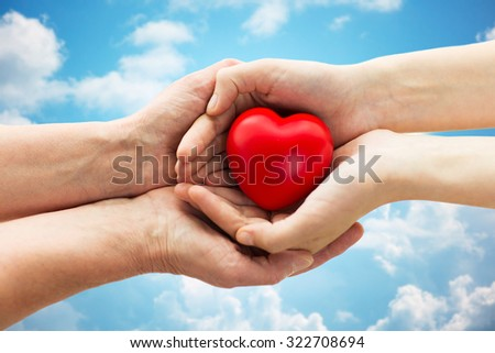 people, age, family, love and health care concept - close up of senior woman and young woman hands holding red heart over blue sky and clouds background #322708694