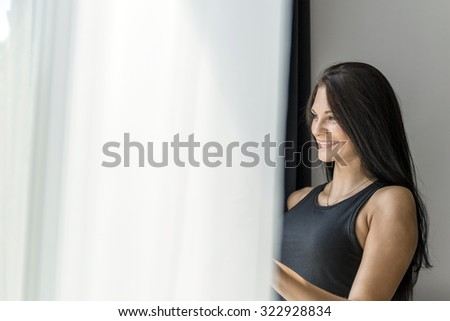 Happy beautiful young woman staring out the window #322928834