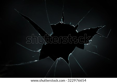 broken cracked glass with big hole over black background Royalty-Free Stock Photo #322976654