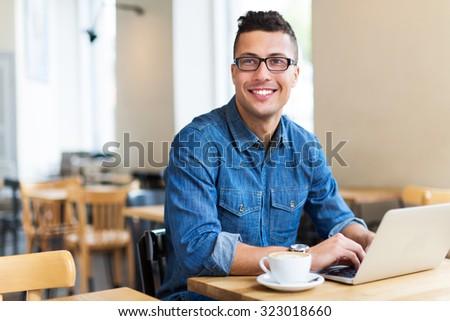 Young man using laptop at cafe  #323018660