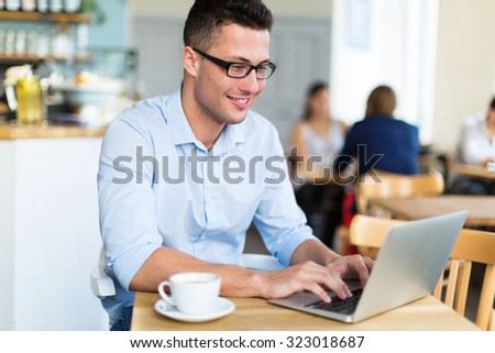 Young man using laptop at cafe  #323018687