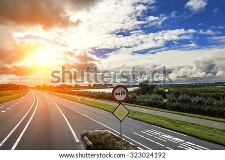 Car Highway at sunset and contrast cloudy sky. #323024192
