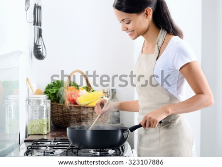 Woman standing by the stove in the kitchen, cooking and smelling the nice aromas from her meal in a pot Royalty-Free Stock Photo #323107886