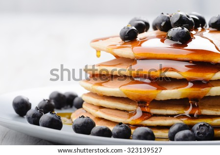 Delicious pancakes close up, with fresh blueberries and maple syrup Royalty-Free Stock Photo #323139527