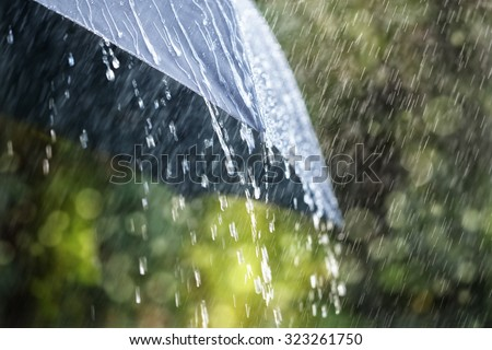 Rain drops falling from a black umbrella concept for bad weather, winter or protection Royalty-Free Stock Photo #323261750