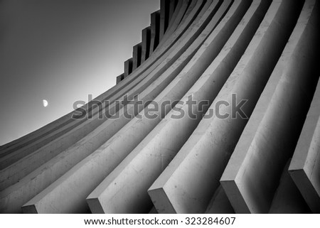 Black and white image of concrete roof beams sweeping down dramatically in curves with the moon rising in a dusk sky. #323284607