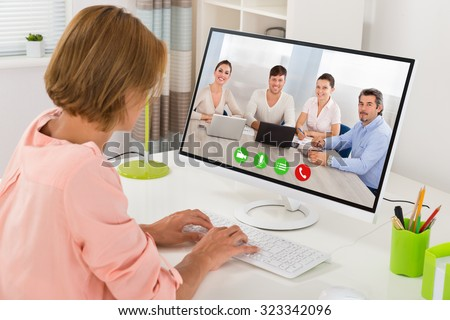 Young Woman Videoconferencing With Colleagues On Computer At Desk #323342096