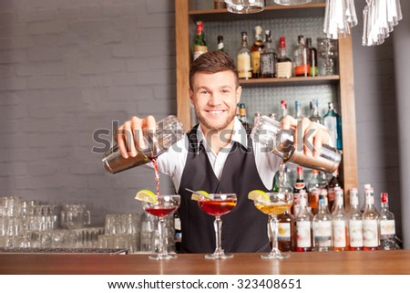 Attractive young bartender is preparing cocktails in pub. He is standing and holding two shakers. The man is pouring mixed drink into glasses. He is looking at camera and smiling #323408651