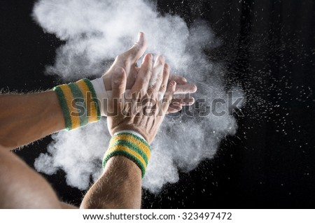 Taped hands of gymnast clapping white chalk powder into a cloud against dark background