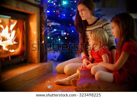 Young mother and her two little daughters sitting by a fireplace in a cozy dark living room on Christmas eve #323498225