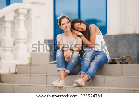 girls friends laughing and outdoor. Young pretty hipster girls friends having fun outdoor in summer on the street. Vintage lifestyle trendy portrait.Two women friends laughing   #323524781