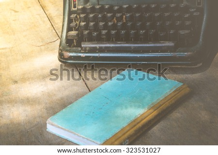 Vintage typewriter and a notebook on a wood table , process in vintage style