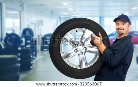 Smiling repairman with tire a in car repair service. #323563067
