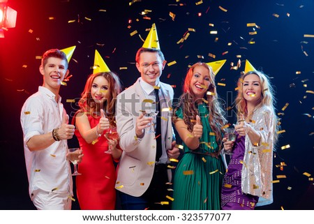 Party and celebration. Group of five happy smiling friends having fun together among confetti in night club. #323577077