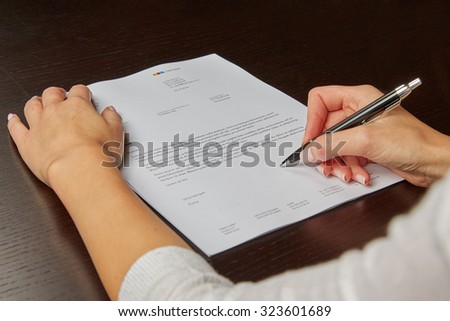 Woman writing on a white sheet of paper, signing a contract #323601689