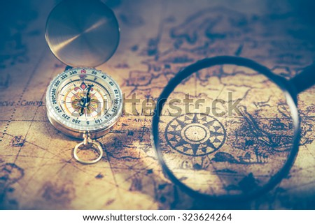 Retro compass on ancient world map, dark vintage style #323624264