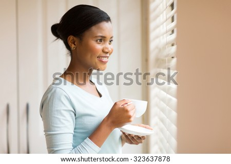 attractive african woman drinking coffee near the window at home #323637878