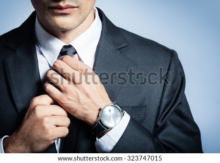 Man in a suit fixing his tie. Royalty-Free Stock Photo #323747015
