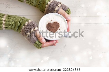 Holding Coffee Latte Cup with Cocoa Shape and Cozy Wool Hands Warmers on Magic Winter Background #323826866