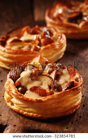 Gourmet mushroom tart in a crisp golden puff pastry base prepared with assorted edible fall or autumn fungi #323854781
