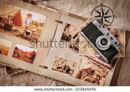 Photo album with photos of travel and vintage old camera on a background of old maps Royalty-Free Stock Photo #323864696