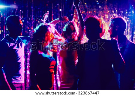 Group of guys and girls dancing in the night club Royalty-Free Stock Photo #323867447