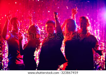 Group of happy friends dancing at party in the night club #323867459