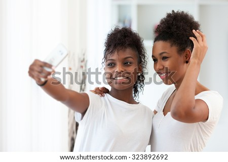 African American teenage girls taking a selfie picture with a smartphone #323892692