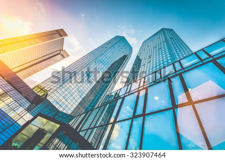 Bottom view of modern skyscrapers in business district in beautiful evening light at sunset with monochrome retro vintage Instagram style filter and lens flare light effect #323907464