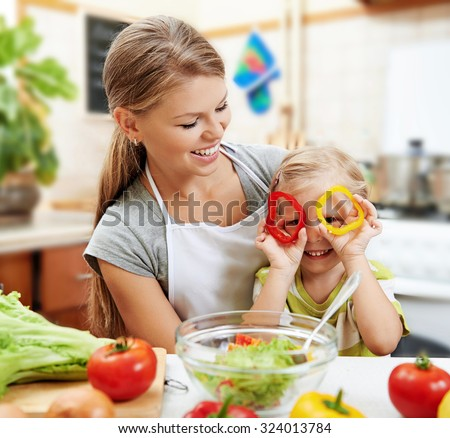 Funny picture of cute little girl holding colorful pepper sitting with her mom at the table in the kitchen.  Young beautiful woman with daughter cooking fresh salad at home.
