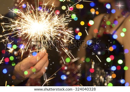 man's hand holding a sparkler during christmas #324040328