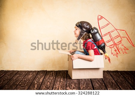 Kid with jet pack. Child playing at home. Success, leader and winner concept Royalty-Free Stock Photo #324288122
