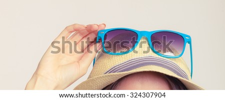 Summer girl holding sunglasses. Happy protected tourist enjoyed vacation. #324307904