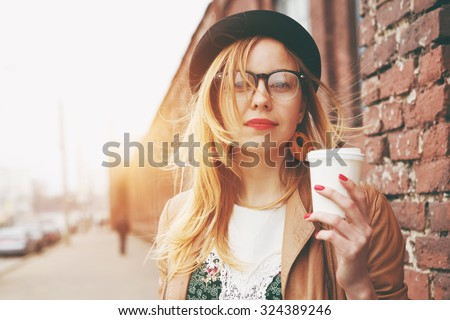 Stylish woman in the street drinking morning coffee #324389246
