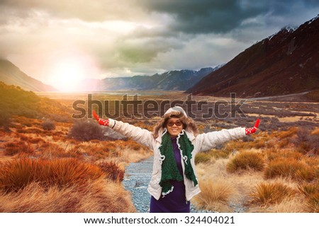 woman traveler wearing winter clothes take a photo with happiness emotion in sun rise natural mountain scene  #324404021