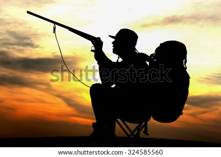 Silhouette of hunter in beautiful sunset on desert with trigger