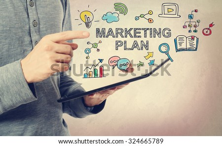 Young man pointing at Marketing Plan concept over a tablet computer