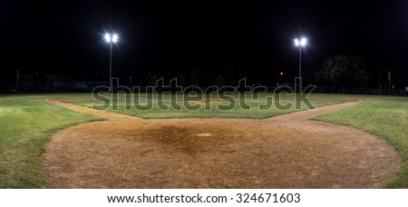 Panoramic night photo of an empty baseball field at night with the lights on taken behind home plate and looking out over the pitcher's mound.
