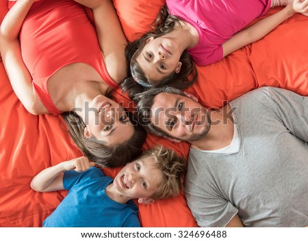 top view of a four people family laying on their big red bed with their heads next to each others. They are wearing colorful tops, smiling and looking at camera. The father has grey hair and a beard #324696488