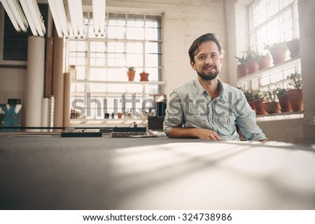Portrait of a small business owner sitting casually in his worskhop studio looking confident and positive