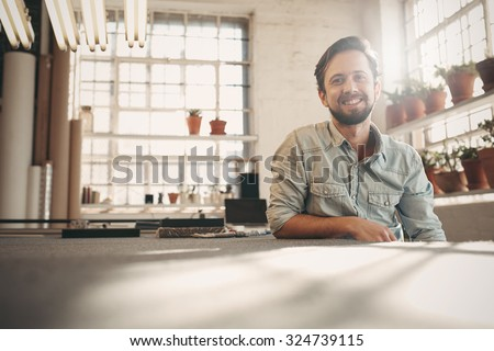 Handsome designer entrepreneur smiling at the camera while relaxing in his studio with gentle sun flare coming in through the window Royalty-Free Stock Photo #324739115